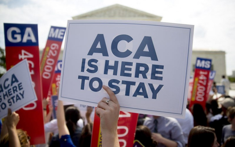 """A demonstrator in support of U.S. President Barack Obama's health-care law, the Affordable Care Act (ACA), holds up a """"ACA is Here to Stay"""" sign after the U.S. Supreme Court ruled 6-3 to save Obamacare tax subsidies outside the Supreme Court in Washington, D.C., U.S., on Thursday, June 25, 2015. The U.S. Supreme Court upheld the nationwide tax subsidies that are a core component of President Barack Obama's health-care law rejecting a challenge that had threatened to gut the measure and undercut his legacy. Photographer: Andrew Harrer/Bloomberg via Getty Images"""