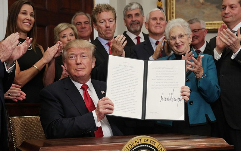 "WASHINGTON, DC - OCTOBER 12:  U.S. President Donald Trump shows an executive order after he signed it as Sen. Rand Paul (R-KY), Vice President Mike Pence, Rep. Virginia Foxx (R-NC) and Secretary of Labor Alexander Acosta look on during an event in the Roosevelt Room of the White House October 12, 2017 in Washington, DC. President Trump signed the executive order to loosen restrictions on Affordable Care Act ""to promote healthcare choice and competition.""   (Photo by Alex Wong/Getty Images)"