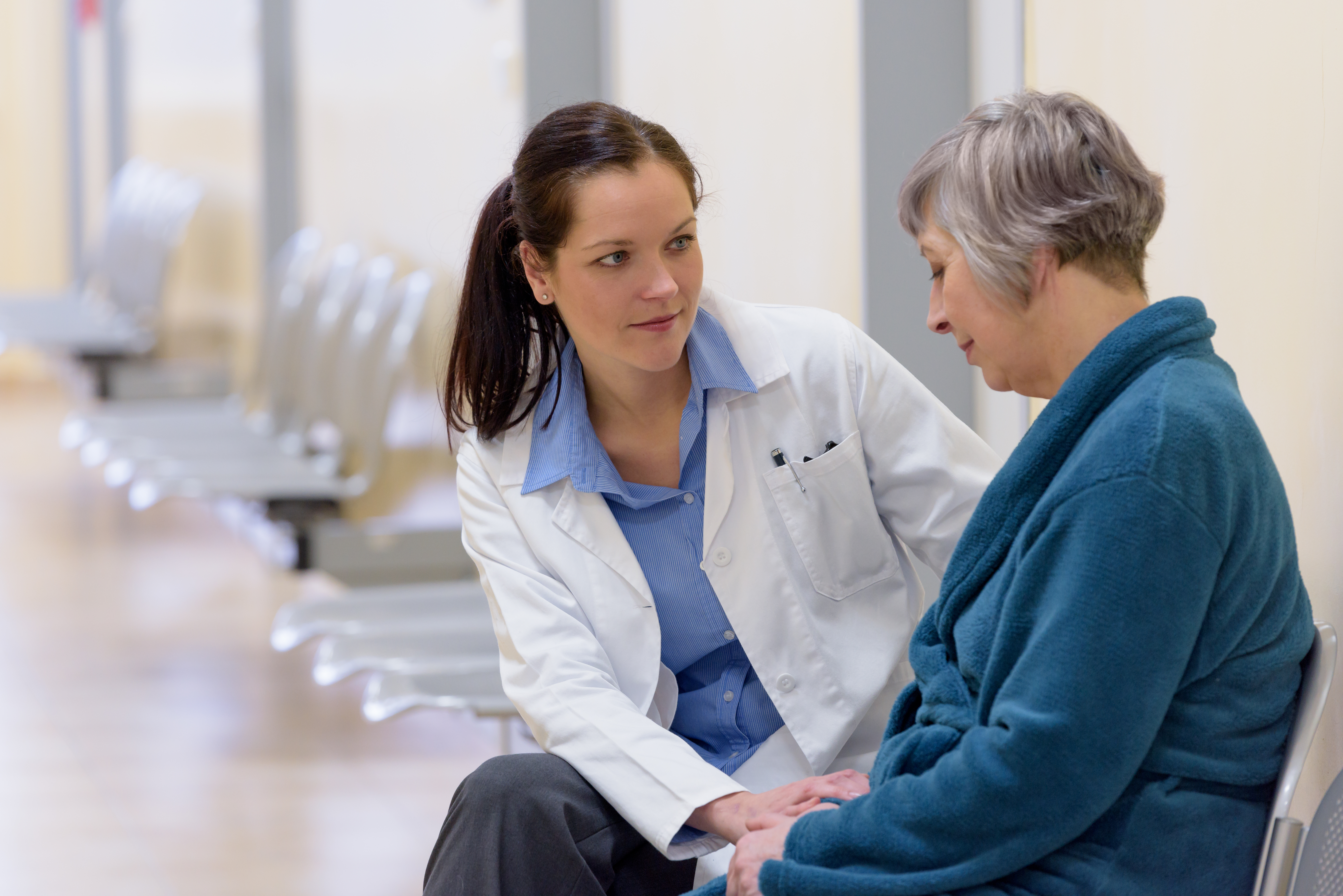 Female doctor comforting senior patient in hospital